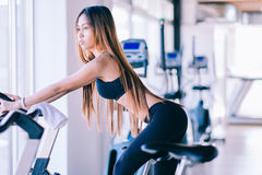 Sport young woman on a stationary bike in the gym.  Stock Photography