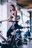 Sport young woman on a stationary bike in the gym.  Royalty Free Stock Image