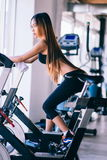 Sport young woman on a stationary bike in the gym.  Royalty Free Stock Images