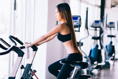 Sport young woman on a stationary bike in the gym.  Royalty Free Stock Photography