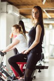 Sport young woman on a stationary bike in the gym. Sport young women on a stationary bike in the gym Stock Photo
