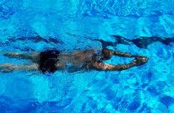 Sport zwemmer in het blauwe water van de pool Stock Afbeeldingen