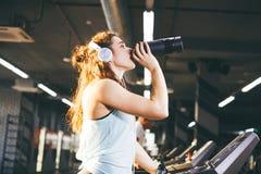Sporta ćwiczenie i odżywianie Piękna młoda kobieta pije proteinę od butelki, czarny potrząsacz w gym bieg na treadm Obrazy Stock