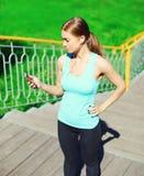 Sporta i sprawności fizycznej pojęcie - piękna młoda kobieta słucha muzyka i używać smartphone w mieście fotografia stock