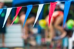 Sporta koloru temblak zaznacza obwieszenie nad pływackim basenem z b, obraz stock