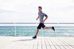 Sporta mężczyzna biega outdoors blisko morza Zdjęcia Stock