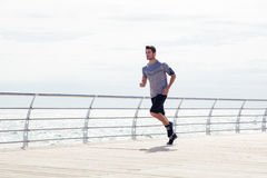 Sporta mężczyzna biega outdoors blisko morza Zdjęcie Stock