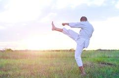 Sporta mężczyzna trenuje sztuka samoobrony karate przy zmierzchem, beauti Obrazy Stock