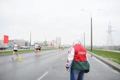 Sporta sędzia ogląda maratonu kurs Popiera grupa ludzi przy ulicami Gomel Fotografia Royalty Free