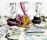 Sporta wygrany pojęcie: trzy filiżanki wśród różnorodnego waluta euro, Fotografia Stock