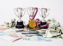 Sporta wygrany pojęcie: trzy filiżanki wśród różnorodnego waluta euro, Zdjęcia Stock