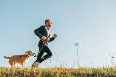 Sportaktivitet med husdjuret Canicross övningar Mannen kör med hans royaltyfri fotografi