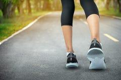 Sportar bakgrund, löparefot som kör på vägcloseupen på sko-, sportkvinnaspring på vägen på soluppgång, kondition och genomkörare arkivfoto