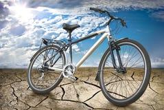 Sportar cyklar i öknen mot bakgrunden av den soliga himlen. Royaltyfri Foto