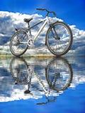 Sportar cyklar mot himlen reflekterad i vattnet Royaltyfri Fotografi