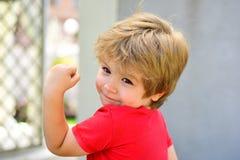 Sportar f?r barn Den starka stiliga pojken visar hans muskler Litet barn efter utbildande genomkörare Sund livsstil little arkivfoton
