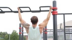 Sportar livsstil, gatagenomkörare Muskulösa manhandtag på stången lager videofilmer