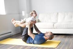 Sportar man är förlovade i kondition och yoga med en hemmastadd behandla som ett barn Royaltyfri Foto
