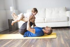 Sportar man är förlovade i kondition och yoga med en hemmastadd behandla som ett barn Fotografering för Bildbyråer