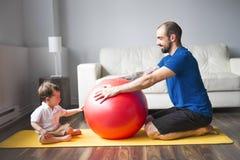Sportar man är förlovade i kondition och yoga med en hemmastadd behandla som ett barn Royaltyfria Bilder