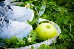 Sportar skor gymnastikskor och äpplet på nytt grönt gräs Arkivfoto