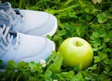 Sportar skor gymnastikskor och äpplet på nytt grönt gräs Selektivt fokusera Royaltyfria Foton