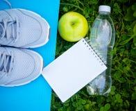 Sportar skor gymnastikskor på matt yoga, flaskan av vatten och äpplet Royaltyfri Foto