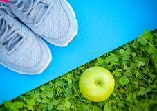 Sportar skor gymnastikskor på matt yoga och äpplet på nytt grönt gräs Arkivfoto