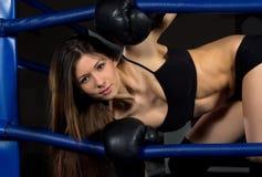 Sportar som boxas kvinnan i svart, boxas handskar i konditionidrottshall Royaltyfri Foto