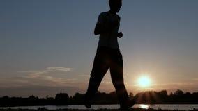 Sportar som joggar på soluppgång En man och en trött tonårs- pojke kör längs invallningen längs floden lager videofilmer