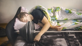 Sportar som kroppsbyggaregrabben sover med den idrotts- skivstången, begrepp av den sunda livsstilen, idrotts- man, vilar efter g Fotografering för Bildbyråer