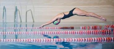 Sportar som simmar, flicka hoppar i vattnet Arkivfoto