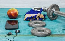 Sportausrüstung Dummköpfe, Hanteln, Sport-Handschuhe, Telefon mit Kopfhörern Stockfotografie