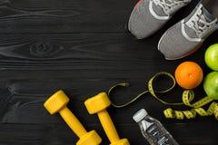 Sportausrüstung und -abnutzung auf dunklem hölzernem Hintergrund, Draufsicht Lizenzfreies Stockfoto