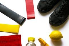 Sportbakgrund av frukter, vattenjämvikt, konditiongummiexpanders, utrustning, tillbehör med kopieringsutrymme på vit Kvinnaidrott arkivbild