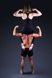 Sportbegrepp - sportigt kvinnasammanträde på skuldror av muskulös mor royaltyfri foto