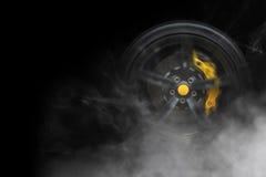 Sportbilhjul med med gulingavbrott och lotten av rökgummihjulet royaltyfri bild