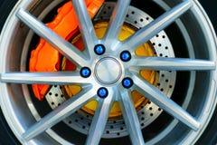 Sportbilhjulet och den orange bromsklämman, blått rullar muttern royaltyfri bild