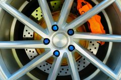 Sportbilhjulet och den orange bromsklämman, blått rullar muttern arkivbild