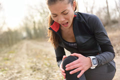 Sportblessure - Lopende geschikte vrouw met kniepijn Stock Fotografie