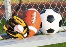 Sportbollar. Fotbollboll, amerikansk fotboll och baseball i handske. Utomhus Arkivfoton