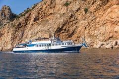 Sportboot gegen ein felsiges Ufer Lizenzfreie Stockbilder