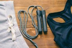 Sportbroek, een sportenbustehouder en een springtouw stock foto's