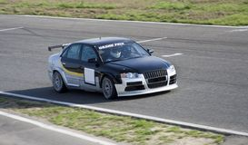 Sportcar in a race. Silver-deep-blue sportcar in a circuit race Stock Photos