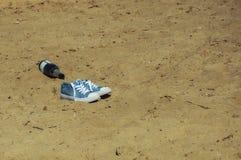 Sporten blauwe tennisschoenen met witte zolen en een fles champagne op het strand stock foto's