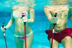 Sporten en gymnastiek onder water in zwembad Stock Foto's