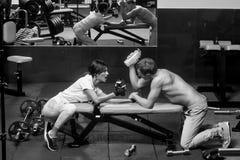 Sporten opleiding Wapen die de spiermens en meisje worstelen bij gymnastiek Stock Foto's