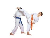 Sporten in paren gerangschikte die oefeningen door atleten met blauwe en oranje riem worden uitgevoerd Stock Foto's