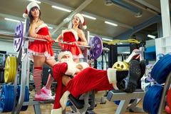 Sporten Santa Claus met meisjes in Kerstman` s kostuums in de gymnastiek stock foto