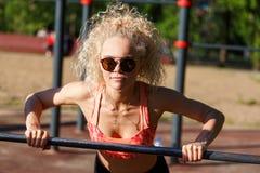 Sporten van het beeld trekt de krullende blonde op sportensimulator uit in park Stock Fotografie